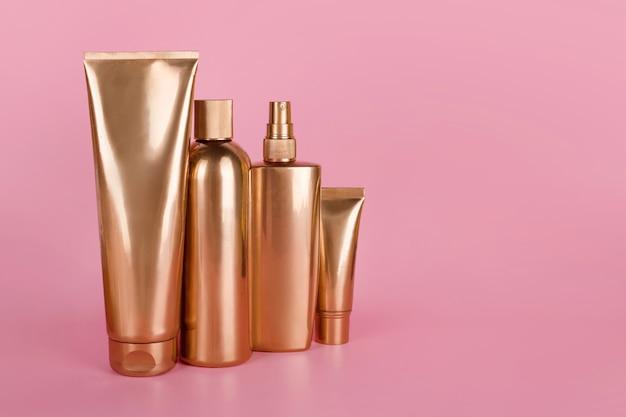 Золотые бутылки, косметические продукты на розовой поверхности
