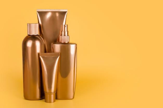 Золотые бутылки, косметические продукты на желтой поверхности
