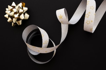 Golden bow and silver star shape silver ribbon on black background