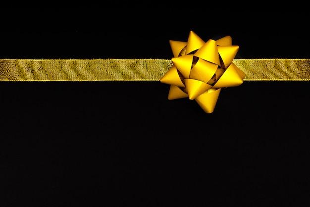 Golden bow on black background, black friday sale concept