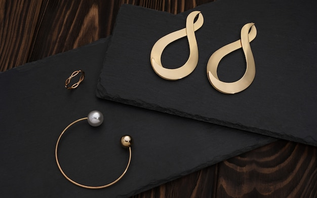 Golden bracelet, ring and infinity symbol shape earrings pair on black plate