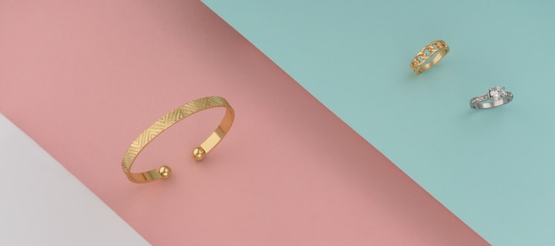 Golden bracelet and and white gold ring with diamonds on colorful background