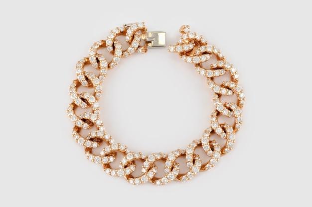 白い背景の上のダイヤモンドと金色のブレスレット