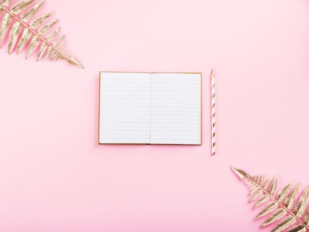 Золотые ветви и открытая тетрадь на розовом