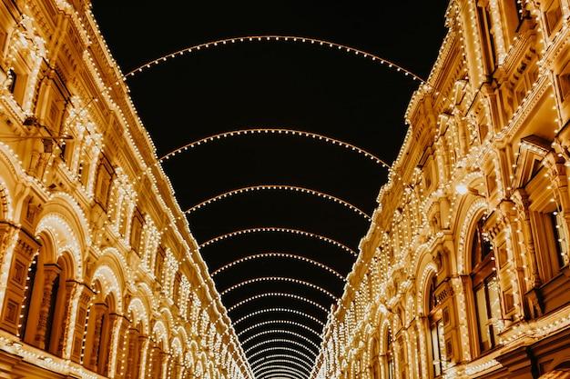 저녁시의 황금 밝은 빛나는 모호한 크리스마스 불빛.