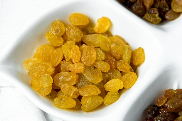 Golden and brown raisins on plate. top view of dried grapes.