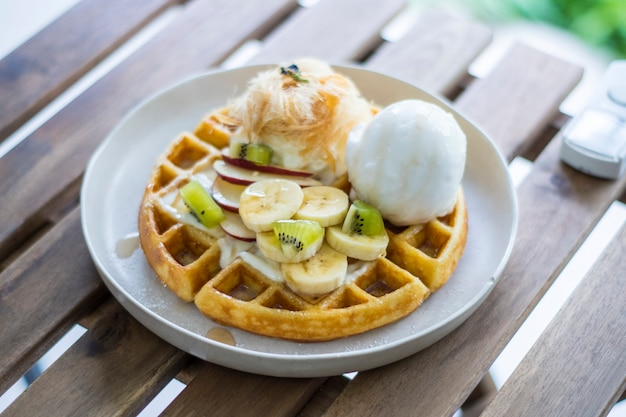 Golden brown waffle topped with ice cream fruit sliced and whipped cream and cotton candy