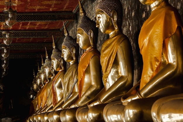 Golden buddha beside old walls in thai temples