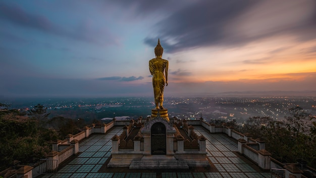 Golden buddha statue in khao noi temple at sunrise time