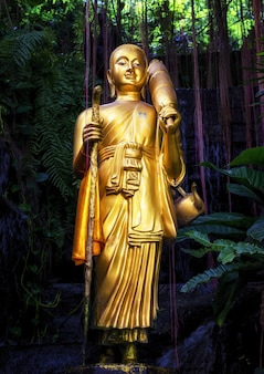 Golden buddha statue and small artificial waterfall at the golden mount at wat saket in bangkok, thailand.