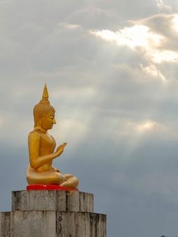 Golden buddha statue with sunlight ray