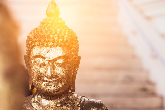 Golden buddha statue with sunlight used for amulets of buddhism religion.
