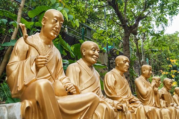 Золотые статуи будды вдоль лестницы, ведущей к монастырю десяти тысяч будд, и пейзаж с зелеными деревьями на заднем плане в гонконге. гонконг - популярное туристическое направление в азии.