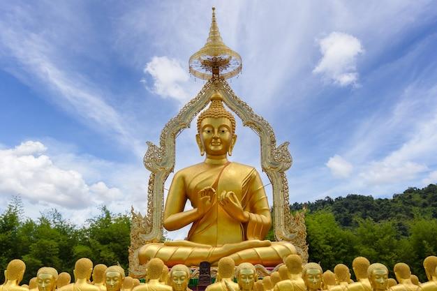 Золотой будда со статуей 1250 учеников в буддийском мемориальном парке маха буча построен по случаю великого периода, накхоннайок, таиланд