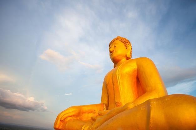 後ろに青い空と黄金の仏像