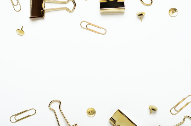 Golden buttons, paper clips and stationery clips on a white background. frame of office stationery. copy space, top view, flat lay.