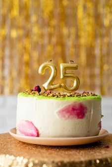 황금 반짝이 배경에 생일 케이크에 황금 초 25
