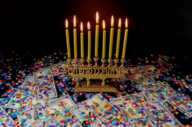 Золотые свечи на меноре и конфетти с деньгами на черной поверхности. еврейский праздник символ хануки.