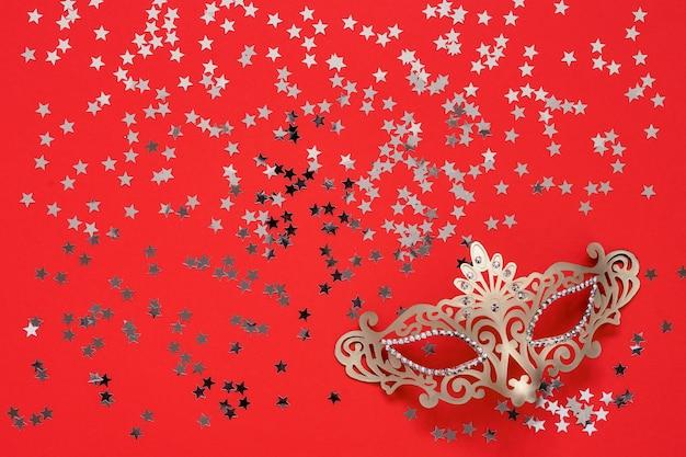 황금 카니발 마스크와 붉은 바탕에 황금 별. 상위 뷰, 복사 공간. 카니발 파티 축하 개념입니다.