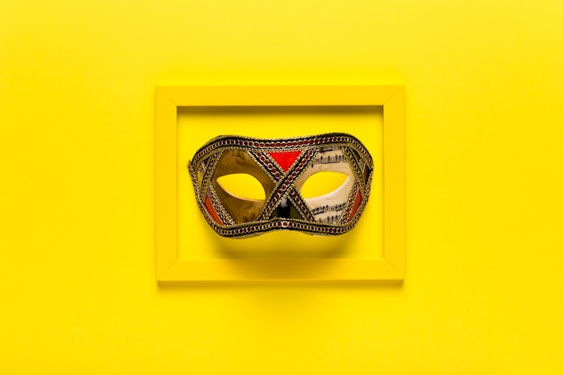 Golden carnival mask in yellow frame