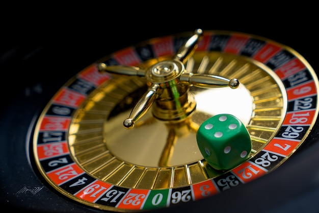 Golden casino theme. high contrast image of casino roulette, poker chips on a gaming table