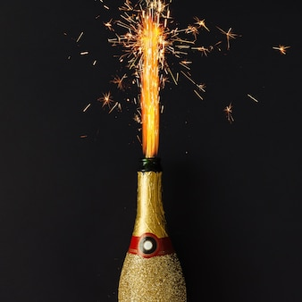 Golden champagne party bottle with firework sparklers on dark surface
