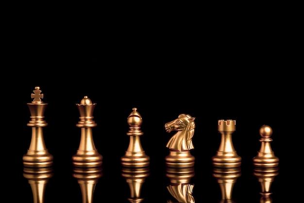 Золотые шахматы включают корабль короля королевы лошади и пешку на черном фоне с отражением.