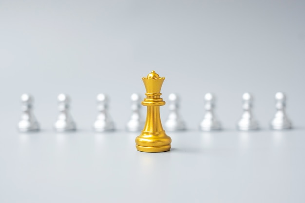 Золотые шахматные фигуры короля или лидер-бизнесмен выделяются из толпы людей серебряных человечков. лидерство, бизнес, команда, работа в команде и концепция управления человеческими ресурсами