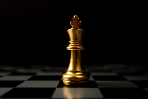 Golden chess king standing alone on the chessboard