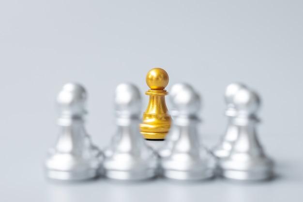 Золотые шахматные пешки или лидер-бизнесмен выделяются из толпы людей серебряных человечков. лидерство, бизнес, команда, работа в команде и концепция управления человеческими ресурсами