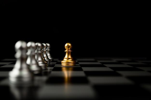 Золотая шахматная пешка, стоящая перед другими шахматами, концепция лидера должна иметь смелость и вызов в соревновании, лидерство и бизнес-видение для победы в деловых играх