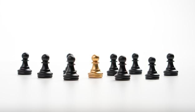 影響力とエンパワーメントを示すためにチームと一緒に立っている黄金のチェスのポーン