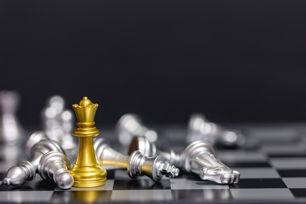 Золотые шахматные фигуры побеждают серебряную шахматную команду на черном фоне