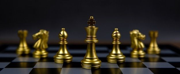 The golden chess team has a king chess stands in the middle of chess board.