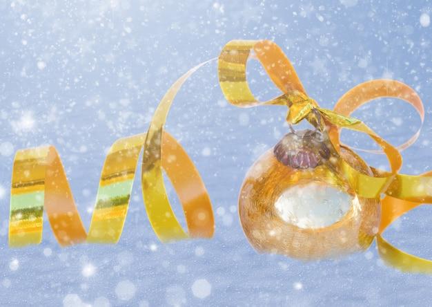 雪の背景に弓と黄金のクリスマスボール