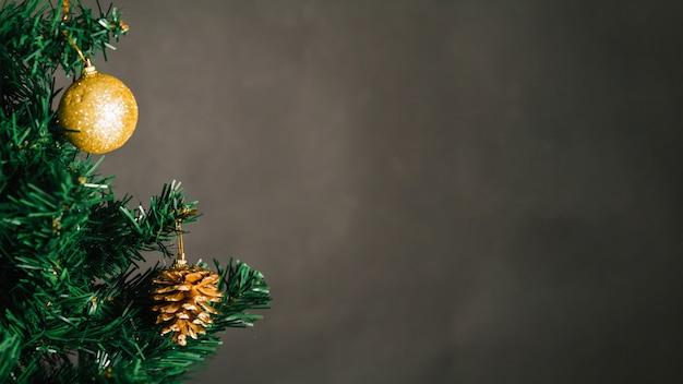 Золотой рождественский шар и сосновый конус на дереве
