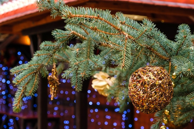 Golden christmas ball and garland hanging on a new year tree branch