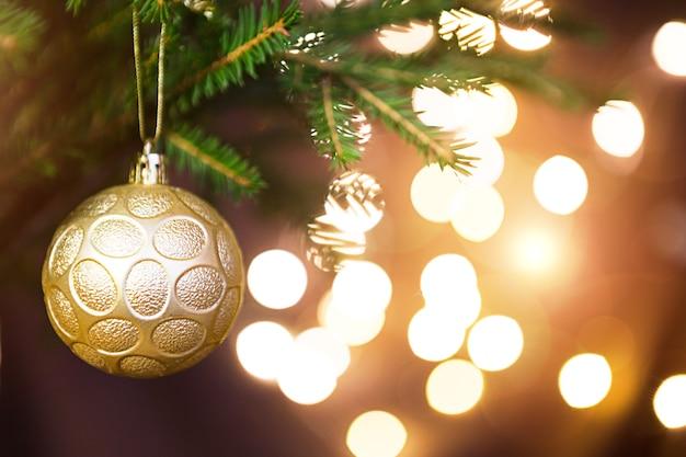 Золотой новогодний шар на живой ветке ели с золотыми огнями гирлянд в расфокусировке. новый год, рождество, праздник фон, боке, копия пространства