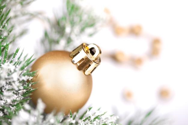 Золотой елочный шар на дереве