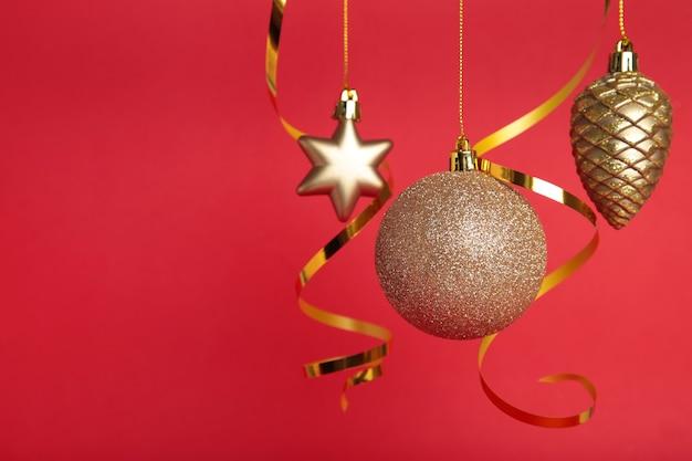 コピースペースと赤い背景の上のリボンとゴールデンクリスマスボール。 2022年の正月。上面図