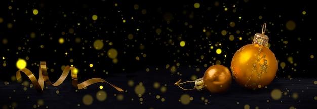 コピースペースが付いている黒い背景のクリスマスカードの上の金色のクリスマスボールおよび曲がりくねったリボン