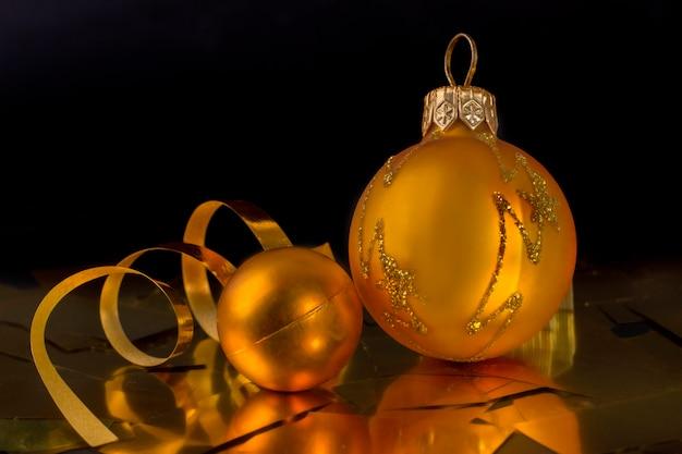 黒の背景にゴールデンクリスマスボールと曲がりくねったリボン。