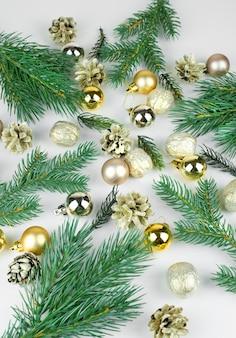 Золотые елочные шары, золотые шишки и ветки елки на светлом фоне