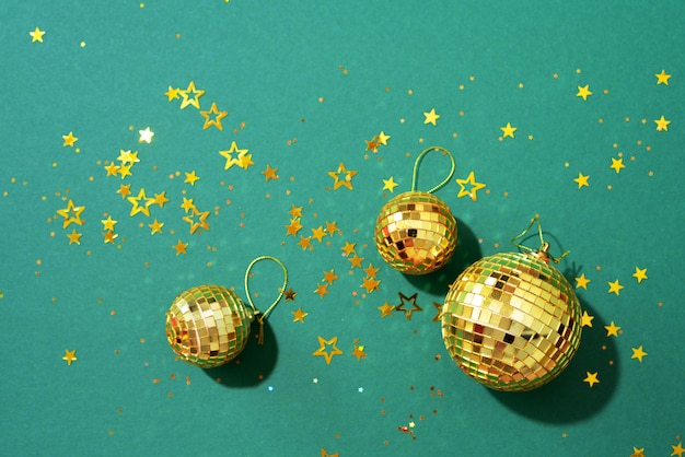 Golden christmas balls with shiny stars on green background