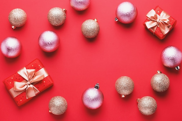혼란스러운 순서로 빨간색 배경에 황금 크리스마스 싸구려와 빨간색 선물 상자, 복사 공간. 반짝이는 포장된 선물과 장식품이 있는 최소한의 평평한 평지