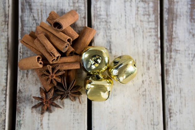 Golden christmas decoration on a wooden table with cinnamon