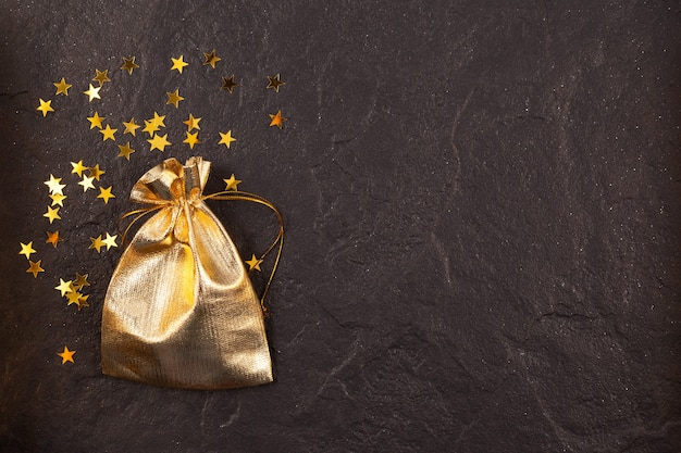 Golden christmas gift bag and golden star-shaped sequins on dark textured stone surface