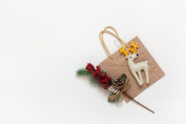 Golden christmas gift bag, white felt toy deer with yellow horns, twig with red berries and needles on white wall, copy space. festive, new year, sales, shopping concept. flat lay. top view.