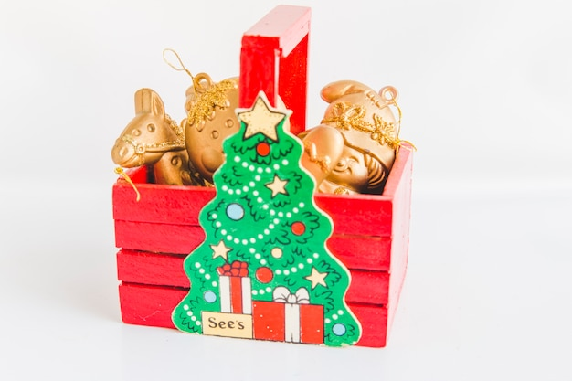 Golden christmas ornaments in the red wooden box with christmas tree on white background
