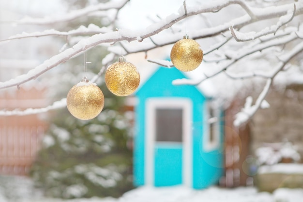 Golden christmas tree balls on the branches and winter snow. christmas balls near fur-trees covered with a snow and small blue wooden house. playground for children at backyard